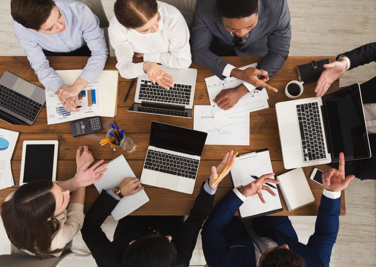Business meeting. Busy people work in office, top view on wooden table with mobile phones, laptop, tablet and documents papers with diagram, corporate background